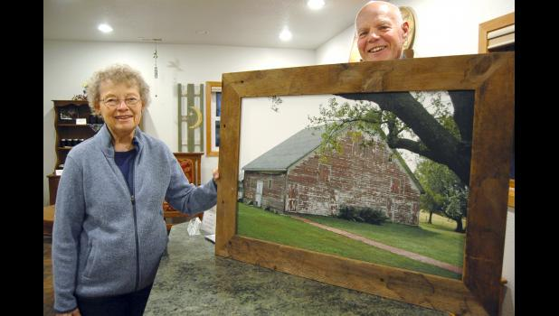 """Nancy (left) and Dean Rogers have put their vineyard and retreat center north of Scranton up for sale. """"It's been a good time, a good experience,"""" Nancy says. They're pictured with a photo of the century-old barn they remodeled for use as a conference/meeting center and lodge. ANDREW McGINN 