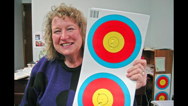 The Rev. Kim Nofel, new pastor of Greater Greene County Presbyterian Ministries, holds up her son's target practice from over the holidays. With the property committee's blessing, Matt Nofel used the Fellowship Hall at First Presbyterian Church in Jefferson to maintain his practice regimen. A member of the U.S. Archery Team, Matt Nofel is among the top-ranked men's archers in the nation. ANDREW McGINN | JEFFERSON HERALD
