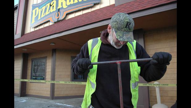 A city employee Wednesday works to turn the water off at Pizza Ranch following an overnight fire. ANDREW McGINN | JEFFERSON HERALD