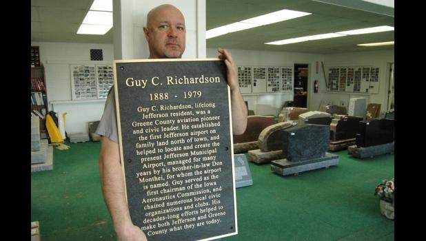 Aaron Sloan, co-owner of Jefferson Monument Works, holds up one of the bronze plaques to be placed around the Square honoring notable Greene County residents.