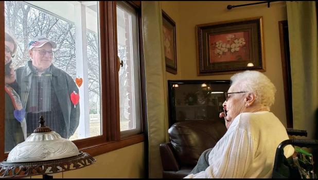 Jeff and Cindy Anderson (left) visit Jeff's mother, Verla, through a window at Regency Park of Jefferson. At nursing homes and assisted-living facilities around town, workers are doing what they can to prevent COVID-19 from breaching their walls. The residents are still in high spirits, said Ali Meiners, Regency Park administrator. CONTRIBUTED PHOTOS