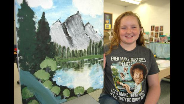 """""""I didn't think I'd watch him like I do,"""" Alivya Smith says of Bob Ross, whose old TV show has found a new generation of fans via Netflix and the internet. With the blessing of Paton-Churdan art teacher Tami Minnehan, 10-year-old Alivya  completed a Ross-style landscape painting in the final weeks of school. ANDREW McGINN   JEFFERSON HERALD PHOTOS"""