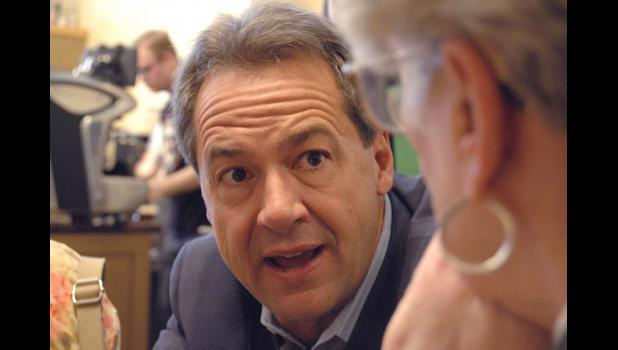 Montana Gov. Steve Bullock crouches down Monday at Greene Bean Coffee to talk with Jean Tucker, of Jefferson, during a campaign stop. ANDREW McGINN   JEFFERSON HERALD