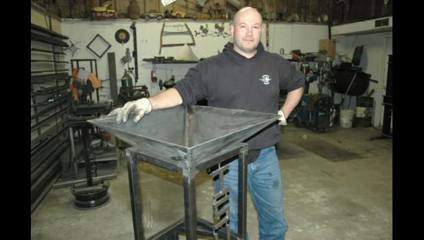 """Shane Olson stands in 2014 next to one of his decorative planters in progress at his shop near Churdan. After two deployments to Iraq, """"I kind of just like it in the middle of nowhere,"""" he told The Jefferson Herald then. Olson is accused of firing on a semi truck June 17 with a rifle. HERALD FILE PHOTO"""