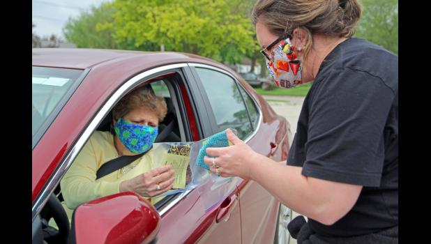 Annie Smith (right), a member of the Greene County Board of Health and principal at the Paton-Churdan Community School, hands out free masks back in May in the parking lot of Trinity Lutheran Church in Jefferson as part of Cover Greene County, an initiative to provide a mask to every resident of Greene County who wants one. ANDREW McGINN | JEFFERSON HERALD