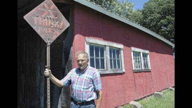 Bob Ausberger, of Jefferson, holds an old sign last week that he said would have marked the spot of a fatal crash on the Lincoln Highway. Ausberger is standing in front of a shed on the property of Randy Monthei, who recently uncovered a hand-painted sign advertising Portage Tires to travelers a century ago on the highway.