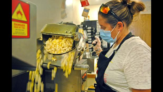 "Anna Pound, an employee at the Sierra Community Theatre, prepares a fresh batch of popcorn Friday on opening night of ""Coco."" Only four customers attended that night's showing. Amid the pandemic, moviegoers simply aren't coming back. ANDREW McGINN 
