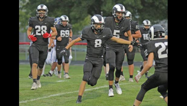 Greene County's Max Riley (8) celebrates with Bryce Stalder (5) and Nate Black (28) following a first quarter touchdown, one of the Rams' five in the opening frame, which led to a decisive 63-0 win over Perry Sept. 3 in Jefferson.  BRANDON HURLEY | JEFFERSON HERALD
