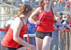 Greene County's Natalie Heupel (right) hands the baton off to Olivia Shannon during the sprint medley relay at the annual Ram Early Bird Relays Monday in Jefferson. The Rams finished third with a time of 2:00.61.  BRANDON HURLEY   JEFFERSON HERALD